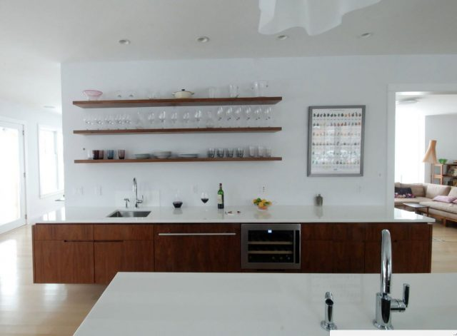 Dark wooden open shelves in a white kitchen