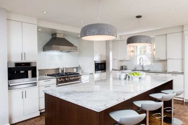 Large pendant lamps over an island in a white kitchen