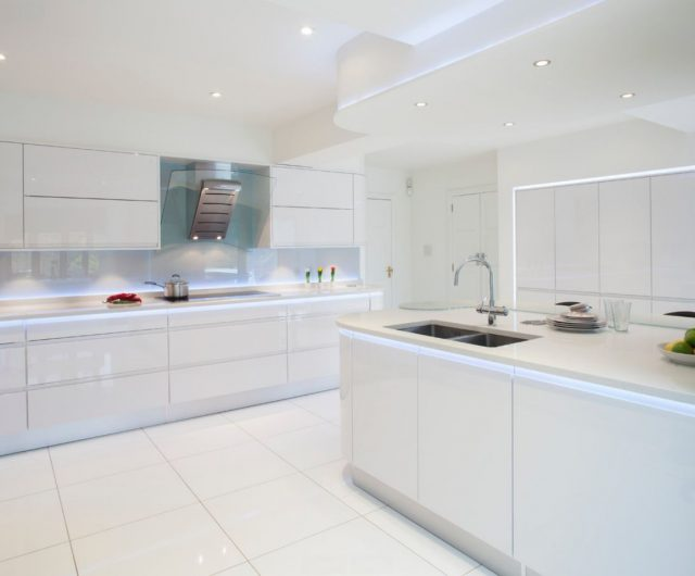 White floor tiles and white ceiling with spotlights in the kitchen