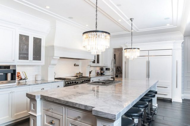White kitchen with marble countertops and black bar stools (2)