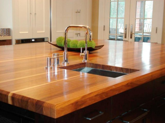 Kitchen island with wooden countertops and dark cabinets